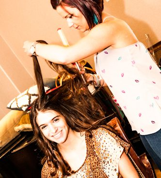 young woman having her hair styled