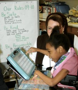 girl working with augmentative communication device with teacher looking on